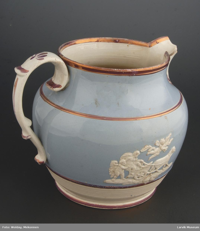 Form: utpressede hvite relieffer Farge: blåglasert utvendig, hvit innvendig. hvit tut og hank. hvit nederst. lilla glasur langs kantene, på tut og hank i 2 horisontale striper.