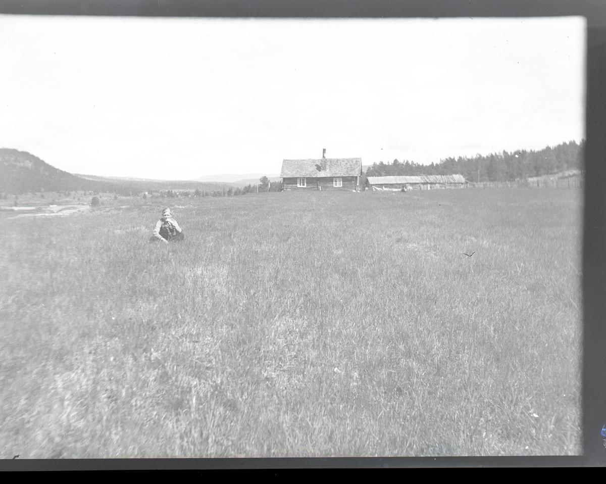 Gutt som sitter på en stølsvoll foran et sel og et fjøs. Skog og fjell i bakgrunnen.