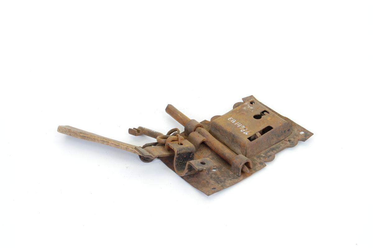 Form: Lås: rektang., 8 skruhull, en mindre kvadrat. låskasse. Dragregel. Nøkkel m. skinnreim, treplate merket S.A.