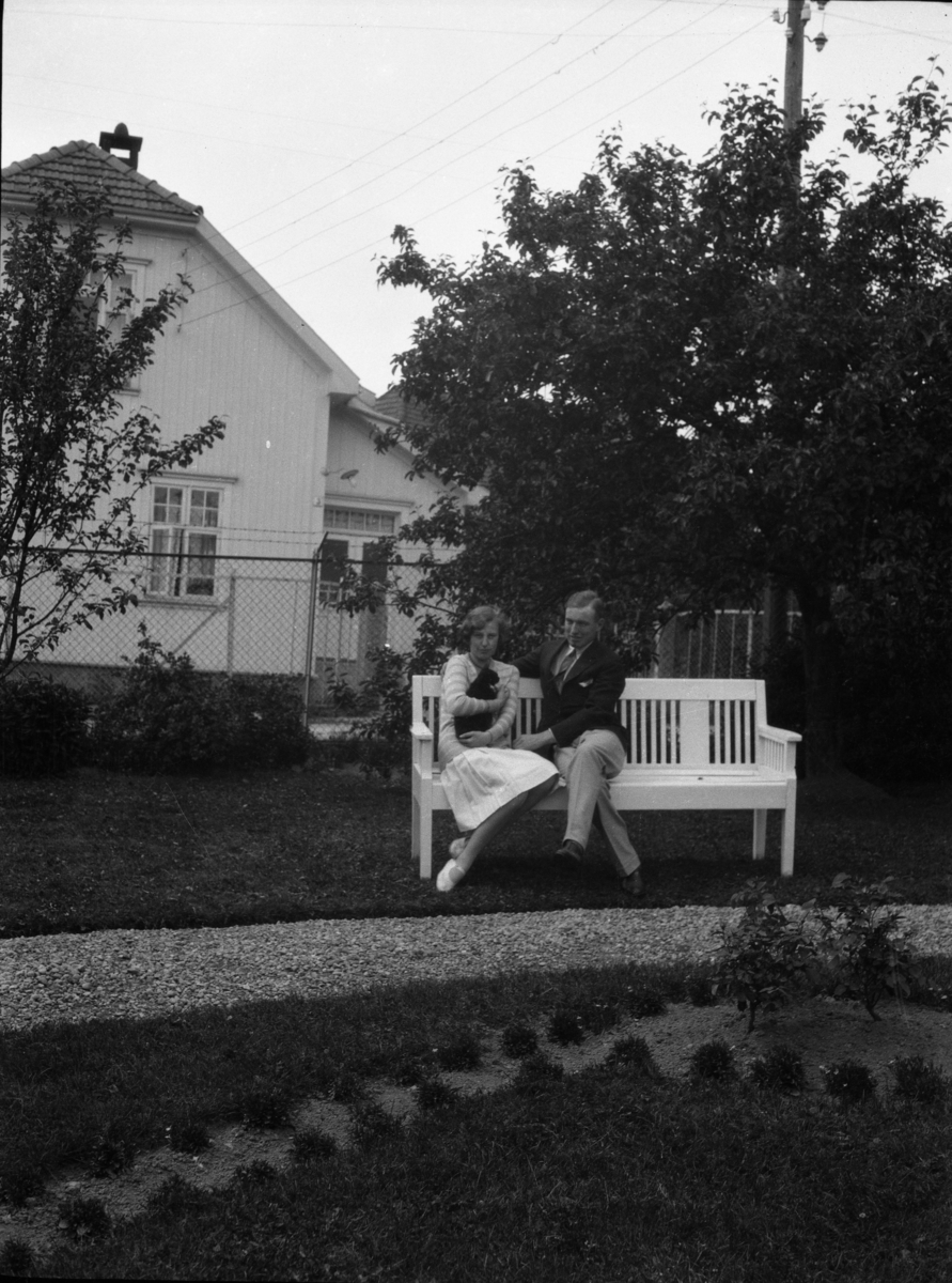 Fotosamling etter Cappelen. Ung kvinne og mann fotografert sittende på en benk i hagen. Kvinnen holder en katt.