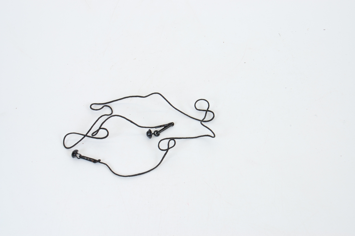Form: snor med en rund knapp i hver ende, ulike, en buet med flat bakside, den andre som en hatt i fasongen med en øyeskrue i under.