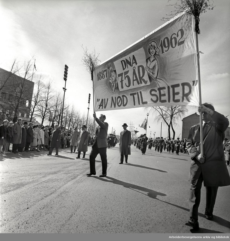 """1. mai 1962 i Oslo.Demonstrasjonstoget.Parole: DNA 75 år.1887 - 1962.""""Av nød til seier"""".Bak ses Einar Gerhardsen"""