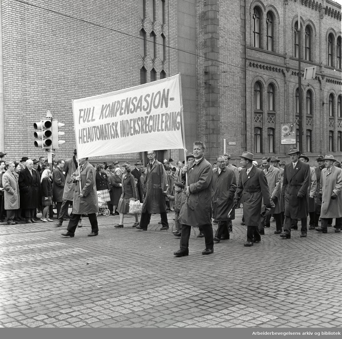 1. mai 1963 i Oslo.Demonstrasjonstog arrangert av Komiteen for faglig enhet med støtte av Sosialistisk Folkeparti (SF) og Norges Kommunistiske Parti (NKP).Parole: Full kompensasjon - helautomtatisk indeksregulering.
