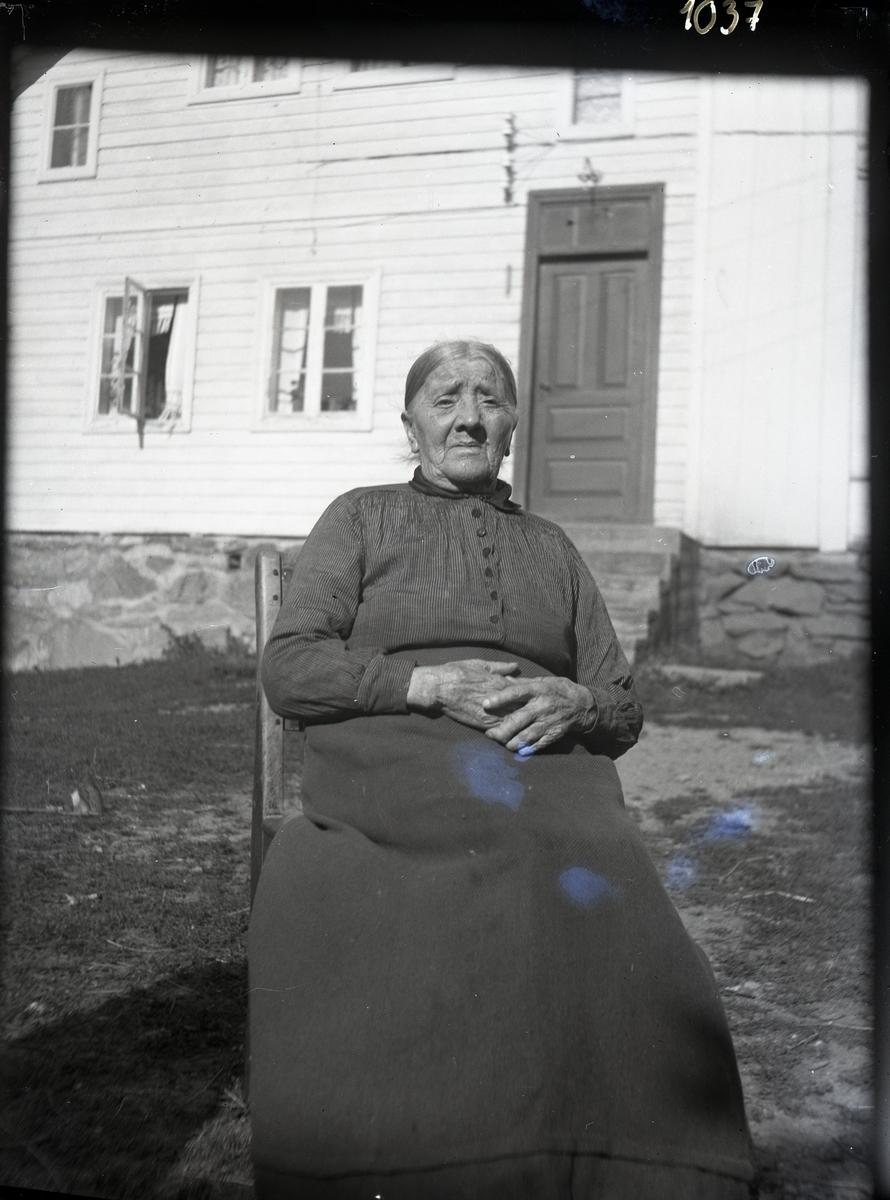 Eldre kvinne sittende på en stol utenfor et hvitt hus i to etasjer. Grunnmuren er støpt med stein. Kvinna er kledd i mørk, stripete bluse med krage og svart langt skjørt.