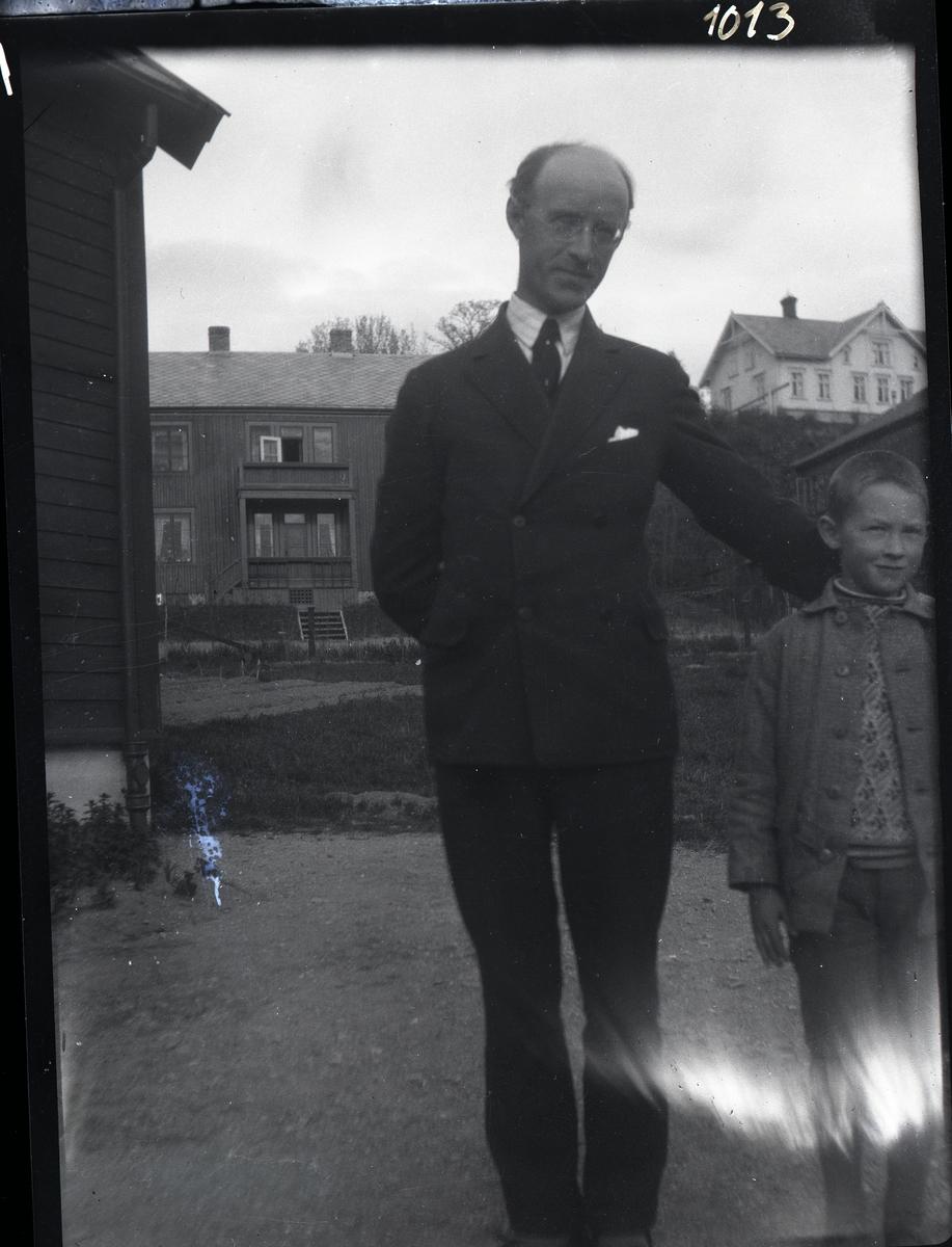 Far og sønn står på en liten grusplass mellom flere ulike hus. Faren er kledd i mørk dress, skjorte og slips. Gutten har grå jakke og mønstret strikkegenser.