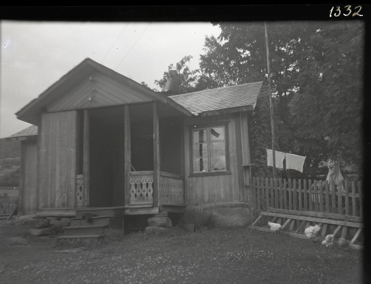Hus med svalgang og tretrapp. Skifertak. Bak et gjerde er det en tørkesnor med klær på. og foran huset går flere høns.