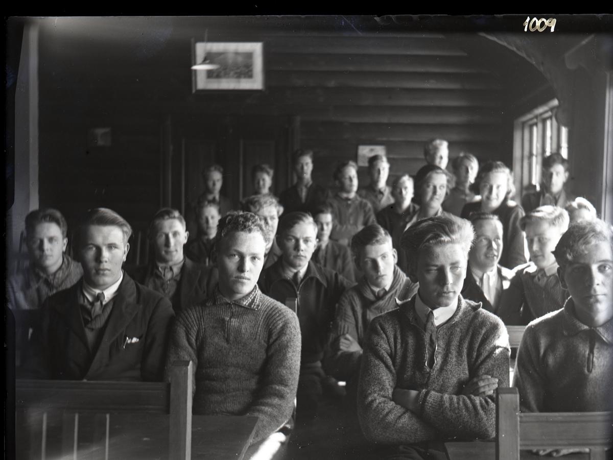 Rundt 20 unge menn og 2 kvinner sitter på benker i et rom med tømmervegger. Elever?