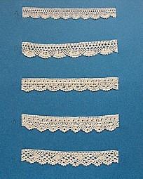 Blått kartongark med fem stycken prover på skånsk knyppling från Gärds härad. Vid varje prov står en stor bokstav. 5 olika solfjädersvarianter. A. 13x 1,5 cm, knypplad med 12 par pinnar B. 13 x 2 cm, knypplad med 12 par pinnar C. 13 x 1,6 cm, knypplad med 11 par pinnar D. 13 x 2 cm, knypplad med 13 par pinnar E. 13 x 1,8 cm, knypplad med 13 par pinnar