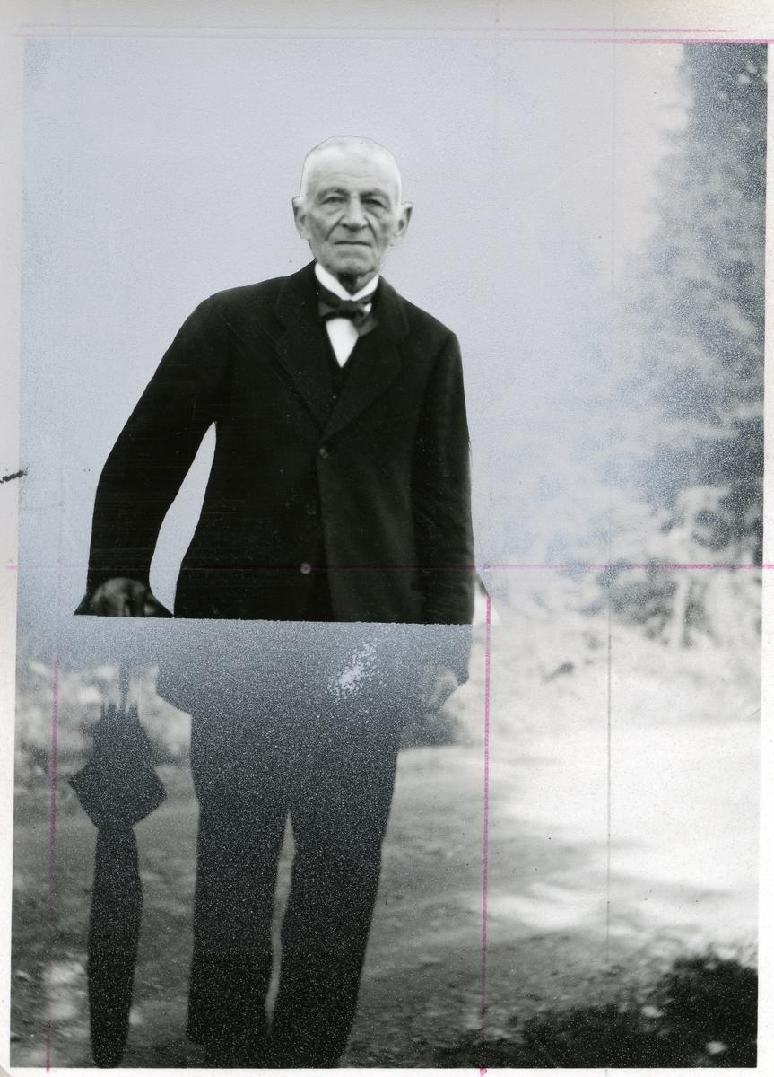 Bildet viser en eldre mann i helfigur. Han er kledd i mørk dress med hvit skjorte og svart sløyfe i halsen. Han støtter seg på en mørk paraply.