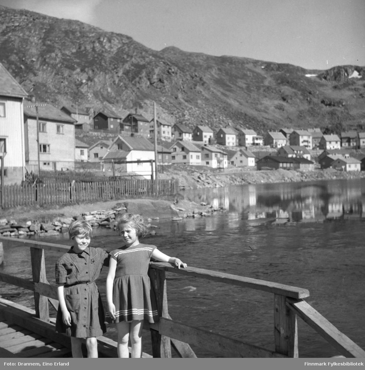 Vigdis Hansen og Turid Lillian står på kaia. I bakgrunnen ser man bygninger. Det er sol og varmt