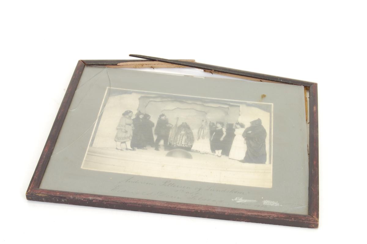 fotoet forestiller 13 personer på en teaterscene, hvorav en av dem er kledt som konge, ei som dronning og ei som prinsesse e.l. og tre som munker/middelalderprester. I forgrunnen står det to menn, en er dverg, med hatt.