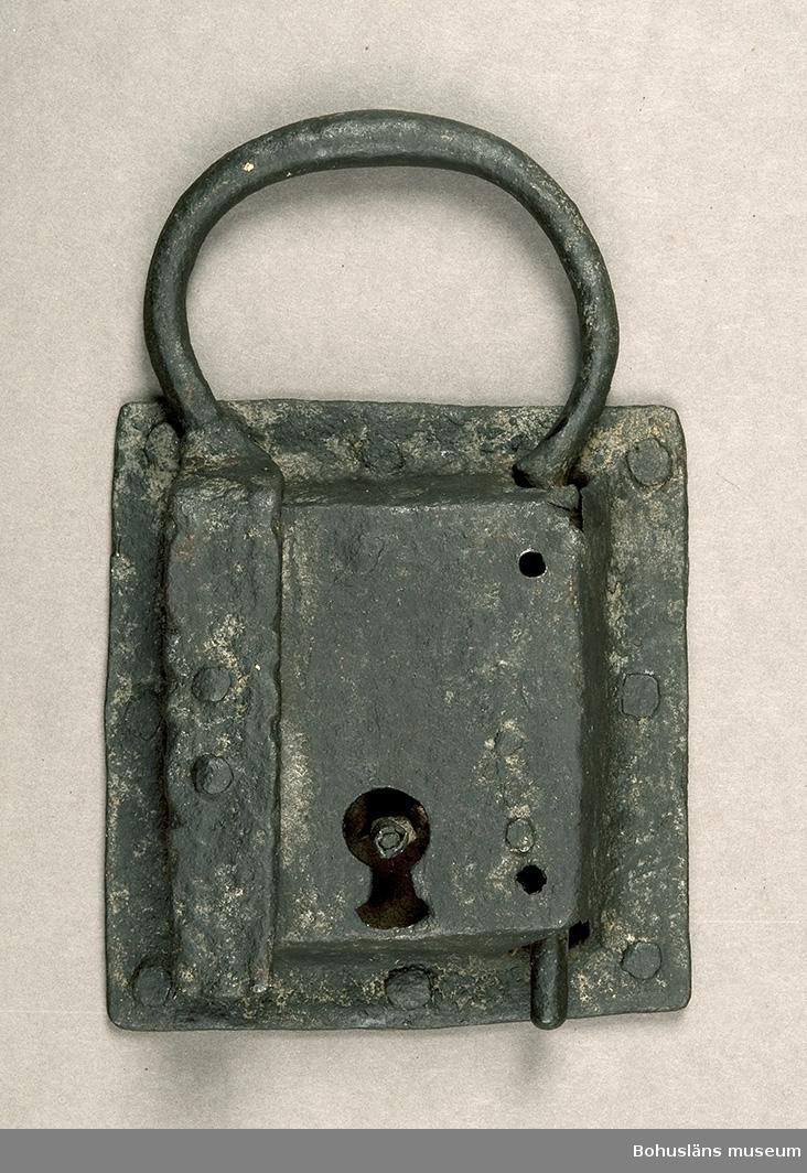 Ur handskrivna katalogen 1957-1958: Järnlås L. c:a 14,8 cm. Br. c:a 13,5 cm. Hänglås av ålderdomlig typ.  Handtagets Br.c:a 10,5 cm. Låset ngt. defekt. Nyckel saknas.   Lappkatalog:  87