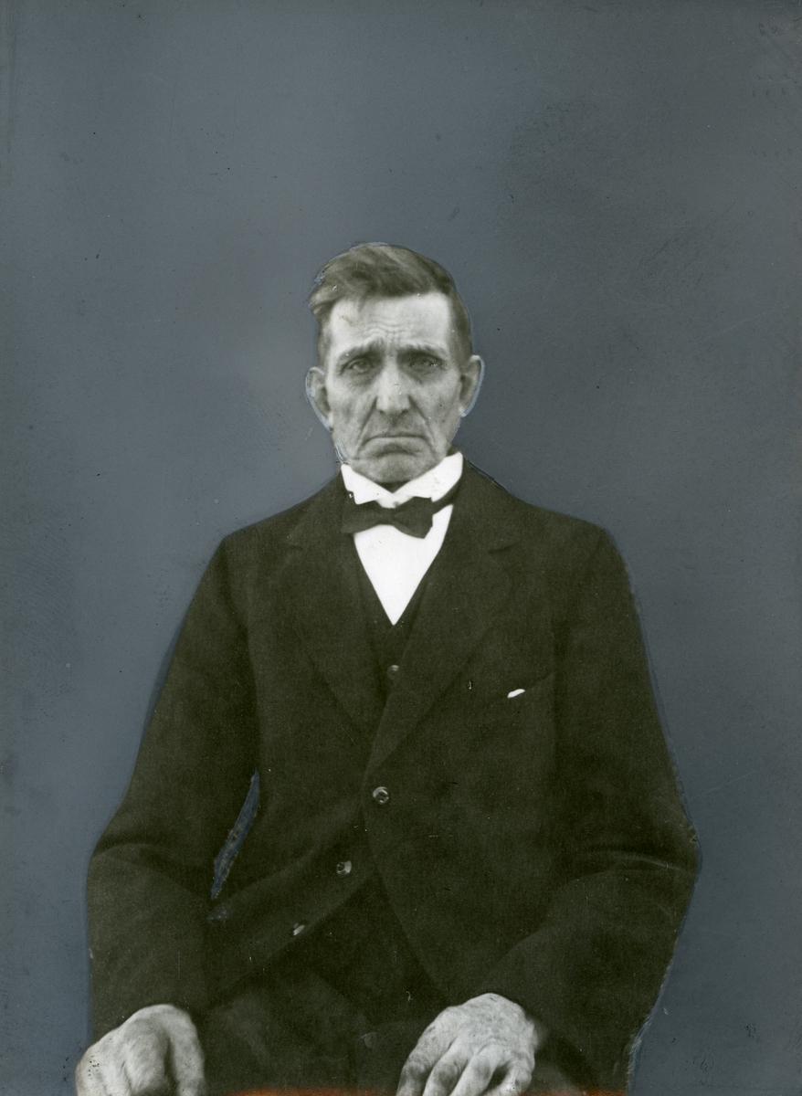 Portrett av sittende mann iført dress og sløyfe.
