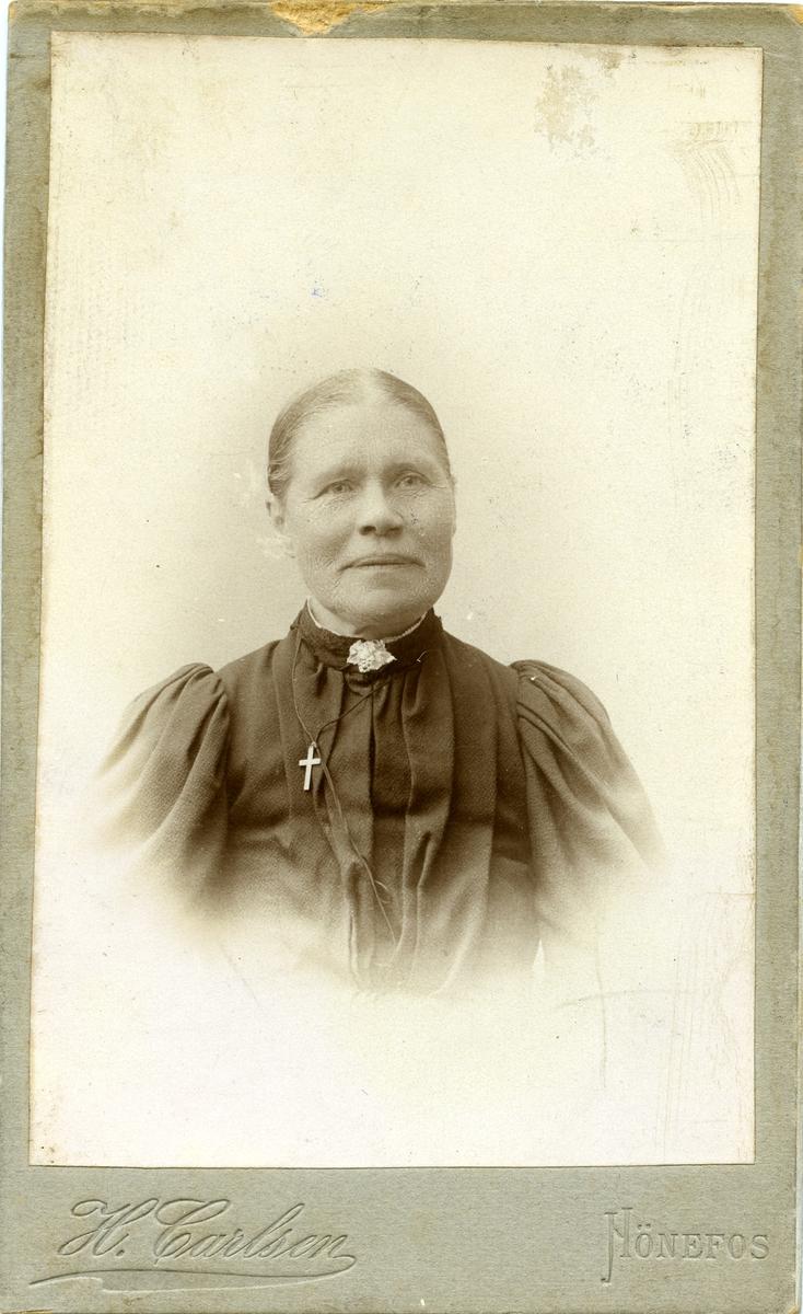 Portrett av en kvinne. Hun er iført svart kjole med korssmykke og halspynt.