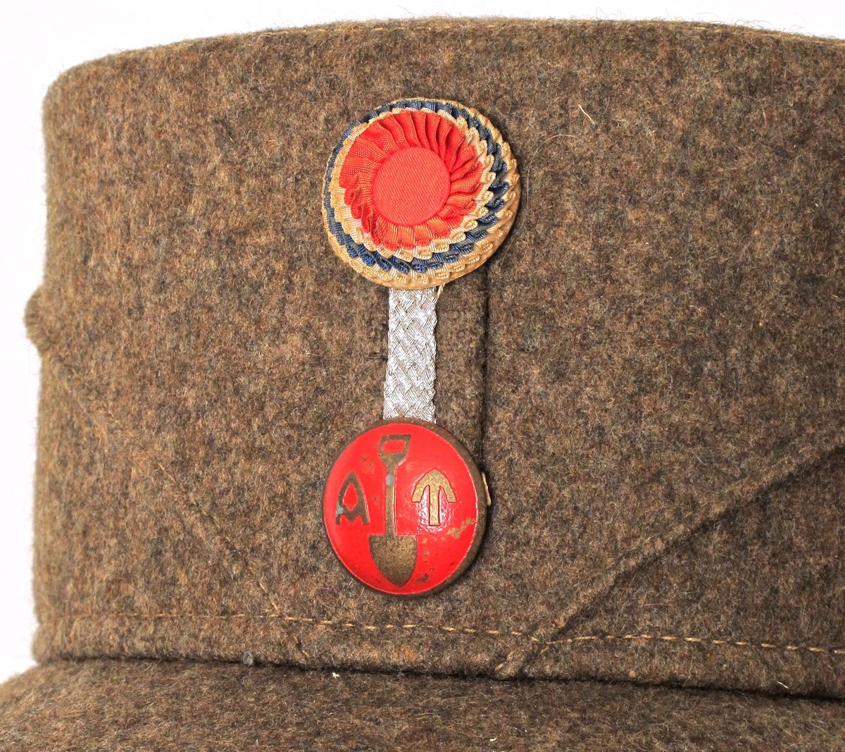 Skyggelue. Rød knapp m. AT samt spade, og rosett i norske farger.