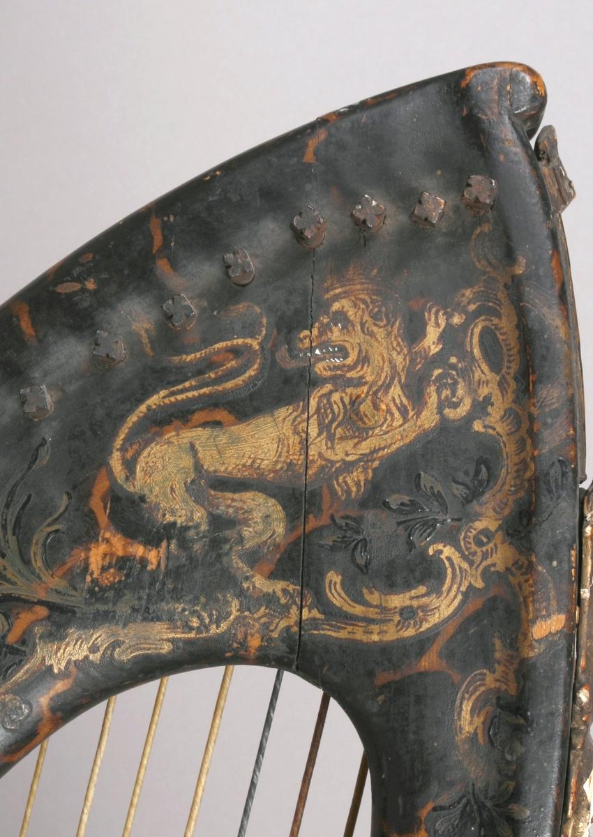 Diatonisk harpe med 32 strenger. Korpus har flat bunn. Lokk av gran med 8 små lydhull. Hvert av lydhullene er forsynt med malt dekor, de forestiller en blomst, hvor  stilk, blader og kronblader er påmalt, og selve lydhullet er blomstens kjerne. Korpus, hals og forstang malt i skillpaddeimitasjon. På hver side av halsen, ved forstangen, malt en forgylt løve. Halsens overside dekorert med akantus og blomster i tre, belagt med gips, deretter forgylt og patinert på rød bunn. Ingen synlig signatur.