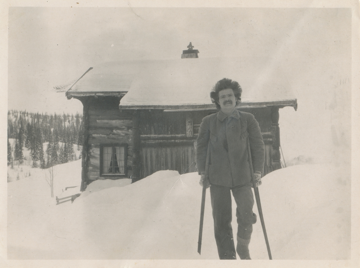 Mann med krykker foran ei hytte i vinterlandskap. Skjeldrup som ung.