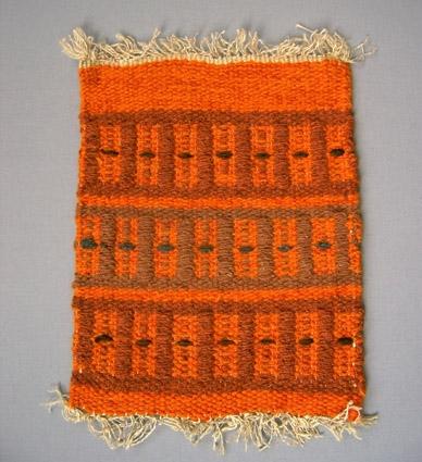Mattprov i rosengång. Linnemattvarp med inslag av nöthårsgarn i  orange och brunt.Provet är från Anna Hådells tid som föreståndarinna, 1961-1975.