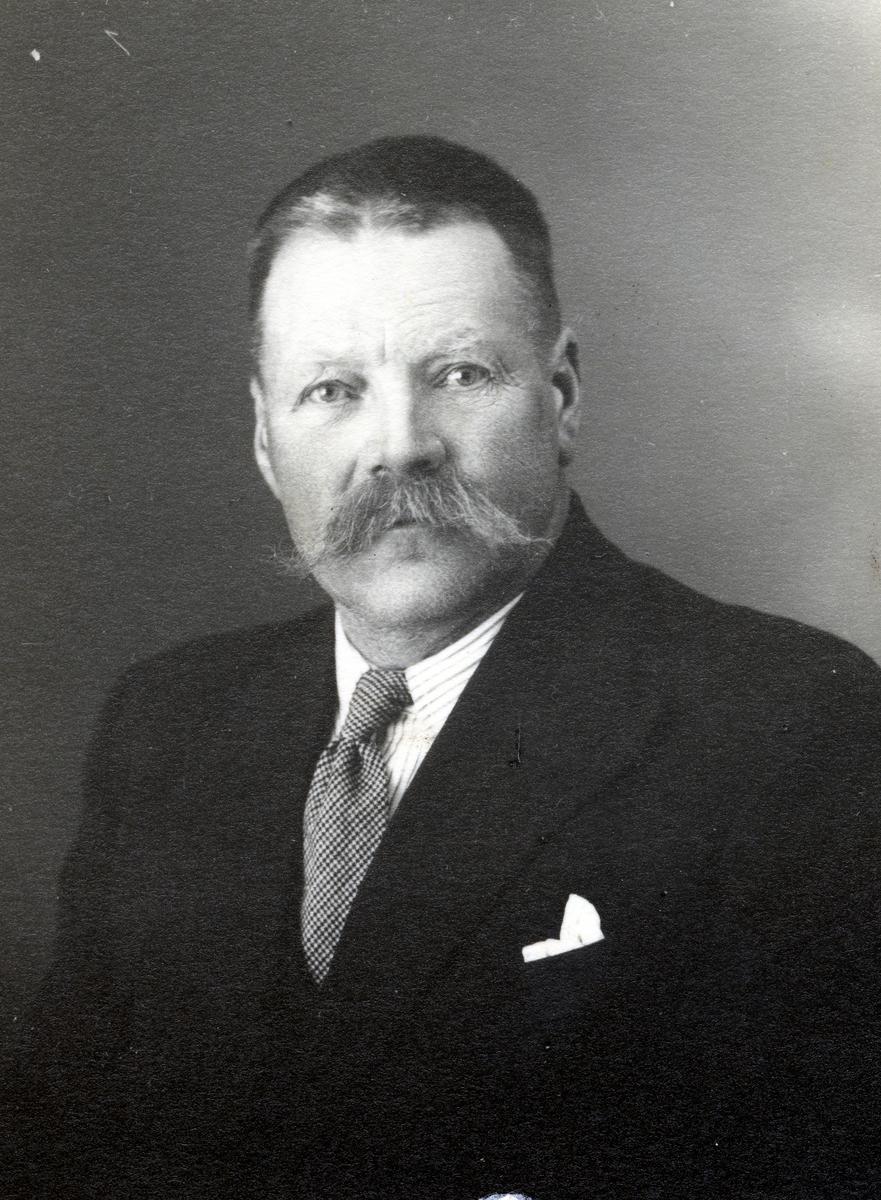 Mann med svart dressjakke, stripete skjorte og rutete slips.