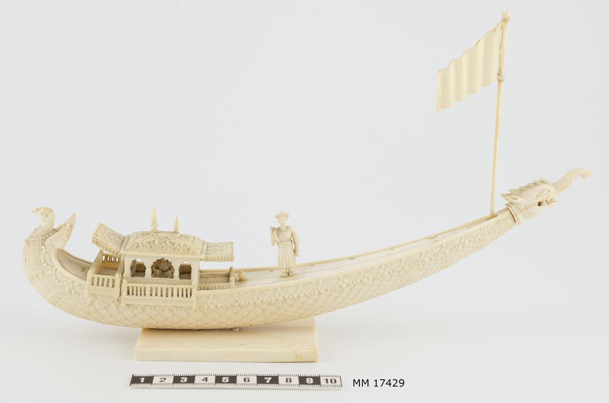 Modellbåt av elfenben föreställande kinesisk båt. Båtens skrov har formen av en bete med en smala, spetsiga änden till akter, som höjer sig högt över vattenlinjen. Fören är utformad som en påfågel med korta vingar samt kroppens och stjärtens fjädrar som ornament längs hela fartygets utsida. Den avsmalnande aktern är längst ut försedd med ett huvud föreställande ett fantasidjur med snabel, huggtänder - som blandning mellan elefant och drake. Närmast fören är en överbyggnad med tak och baldakiner, inuti sitter figur med korslagda ben. Mitt på däck står en man mot babord, hållande en stav lyft i höger hand. I aktern sitter en flagga på en stång. Längs kanterna på däcket är borrade hål, troligen avsedda för placering av figur som ror. Båten är placerad på rektangulär platta 60 x 90 mm.