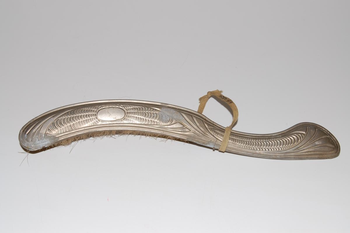 Mønster i metallet bl.a. et ovalt felt med stråler rundt, og striper.