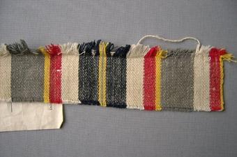 """Vävprov, randigt bolstervarstyg i bomull och cottolin vävt i kypertbindning. Randigt i inslagsriktningen i blått, rött, grått, gult, grönt och vitt. Varp i blått, rött, grått, gult, grönt och oblekt/vitt bomullsgarn nr 16/2. Inslag i cottolingarn. Märkt med påskriften: """"Madrassvar """"Matsgården"""" Bredd c:a 86 cm Pris 14:- pr m. Finns både med inslag av cottolin och lingarn. Finns även c:a 74 cm á 12:- pr. m.""""."""