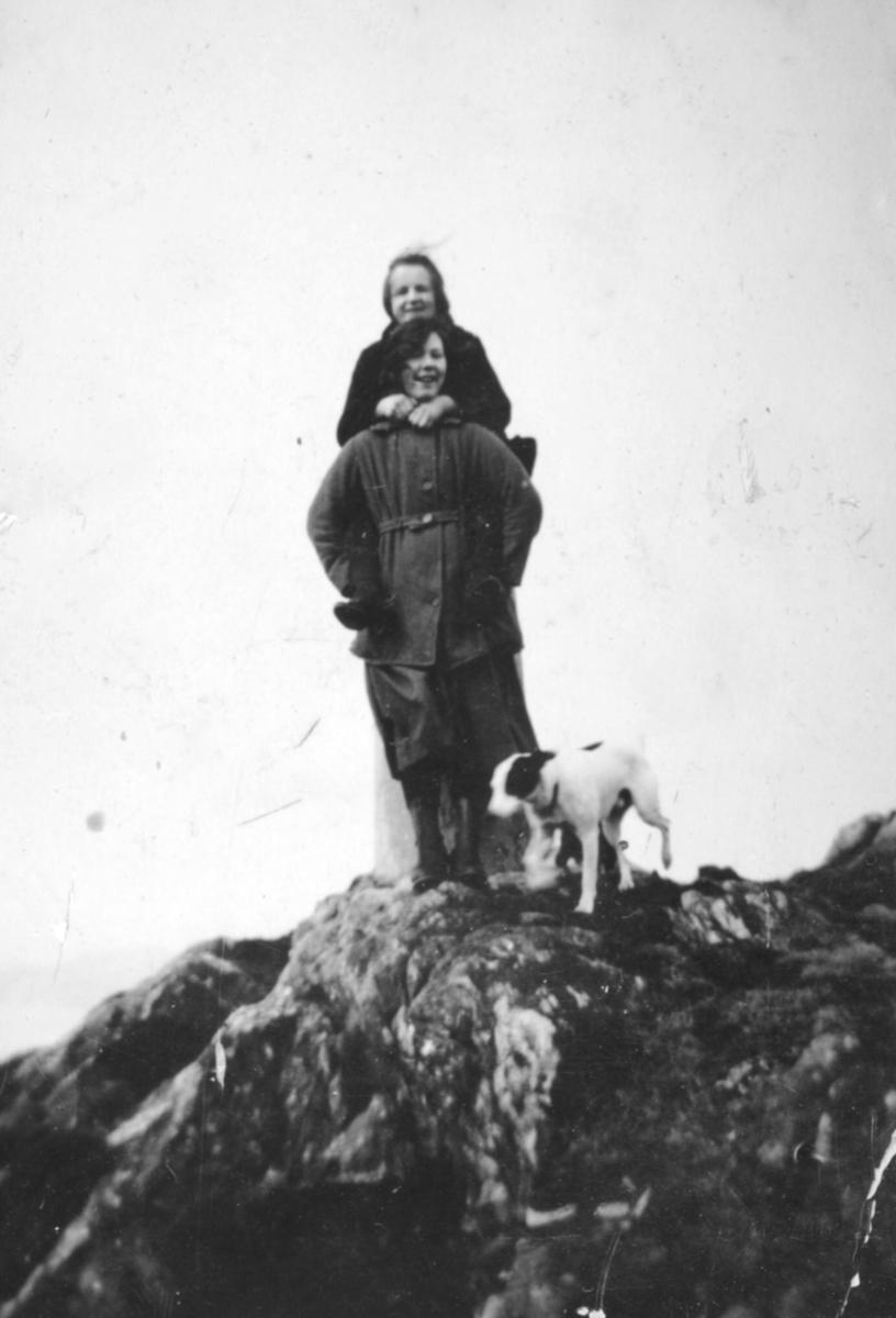 To kvinner og en hund fotografert på en topp. Personer og sted er ukjent, men bildet er sansynligvis tatt i Kvalsund kommune.
