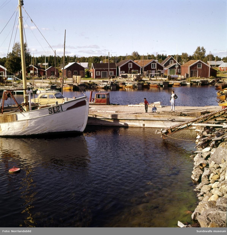 Löruddens fiskeläge med båtar, bryggor och fiskebodar.