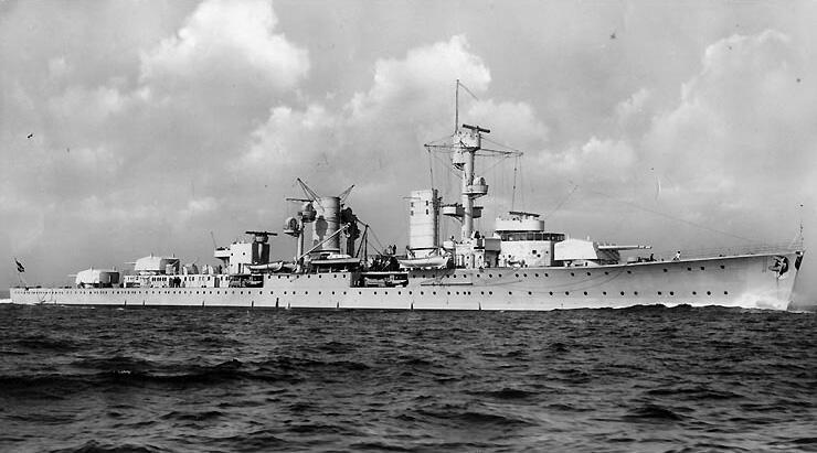 Sort/hvitt bilde av krysseren Karlsruhe på sjøen, sett fra styrbord side. Skyer tårner seg opp i bakgrunnen. (Foto/Photo)