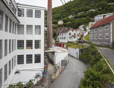 Bygda Salhus utanfor Bergen, med den tidlegare tekstilfabrikken Salhus Tricotagefabrik, fabrikkpipa og ein arbeidarbustadtil høgre.. Foto/Photo