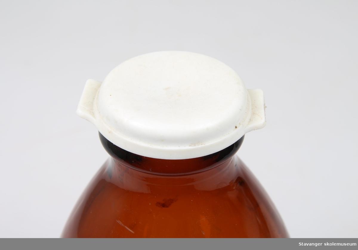 Brun melkeflaske med plastkork.