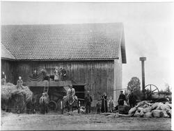 Treskelag og andre hjelpere foran låven på Boksrud i Totenvi