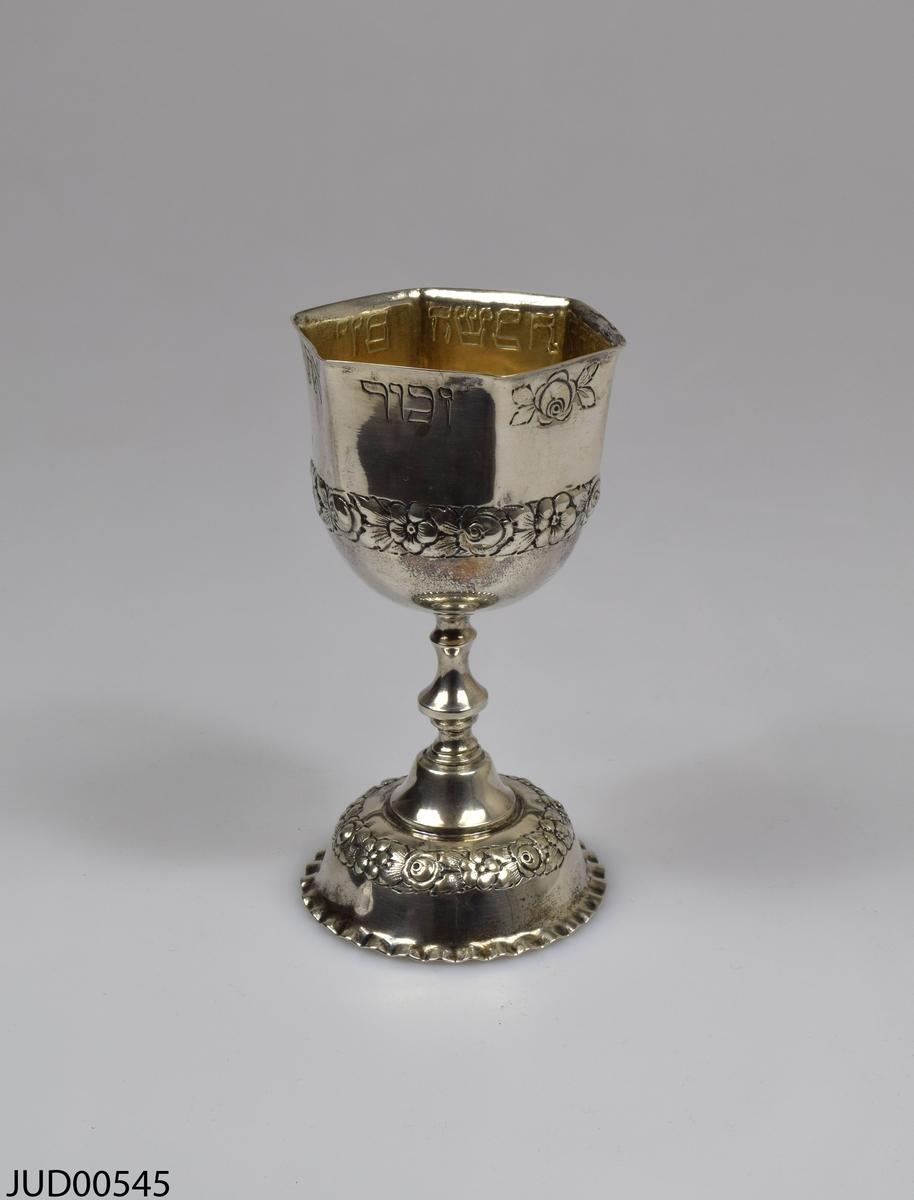 Silverbägare med rund fot och sexkantig cupa. Dekorerad med blommor i relief och ristade hebreiska bokstäver.