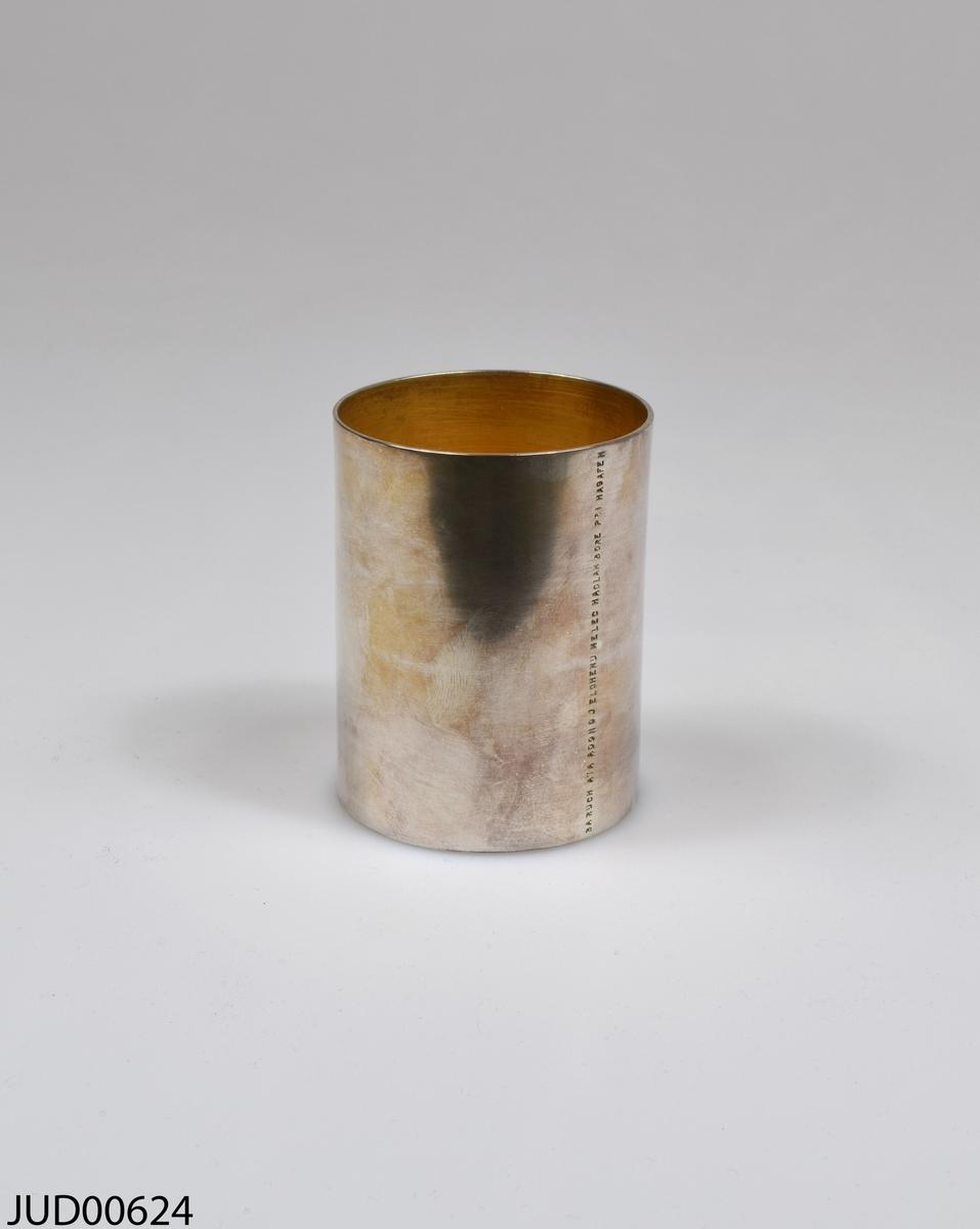 Kiddushbägare tillverkad av silver, och invändigt förgylld. Graverad vertikal text skriven på hebreiska, med latinska bokstäver.
