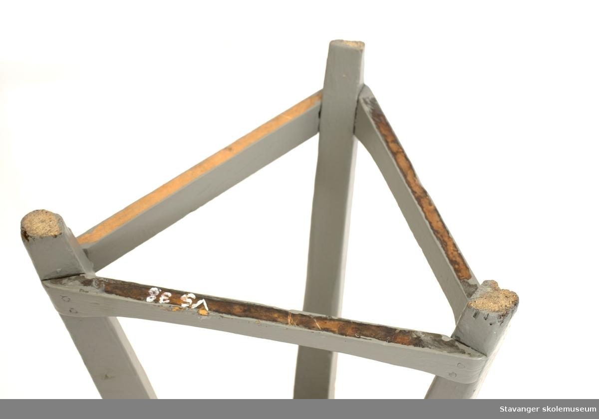 Krakk med tre bein og rundt sete. Sete trukket av skai. Pyntestifter langs kanten. Bein og sprosser er malt grå.