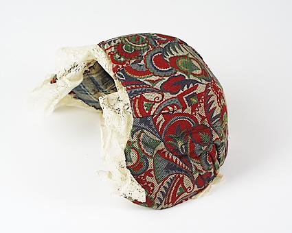 Mössa, typ bindmössa. Mitt fram går mössan ner i liten spets. Längd från öra till öra 37 cm. Längd hjässlinje 21,5 cm. Yttertyg i vitbottnad kattun med tryckta mönster i blått / grönt / rött / gult. Mössan ej hantverksmässigt omklädd. All montering gjord med nåttingstråd. Foder i tuskaftat linne storrutigt i vitt / blått. Fodret klistrat på pappstomme. Hjässlinjens invikning mycket ojämn. Sydd med ojämna fållstygn i nåttingstråd. Ojämn invikning runt mössans ytterkanter. Runt framkanten och ner till vecken på varje sida är en 5 cm bred köpespets fastsydd. Den är lagd i oregelbundna motveck. Spetsens längd är 1,32 m. Den är skarvad på ett ställe och kortsidorna är ofållade. Förstygnsrader i mössans framkant saknas helt.