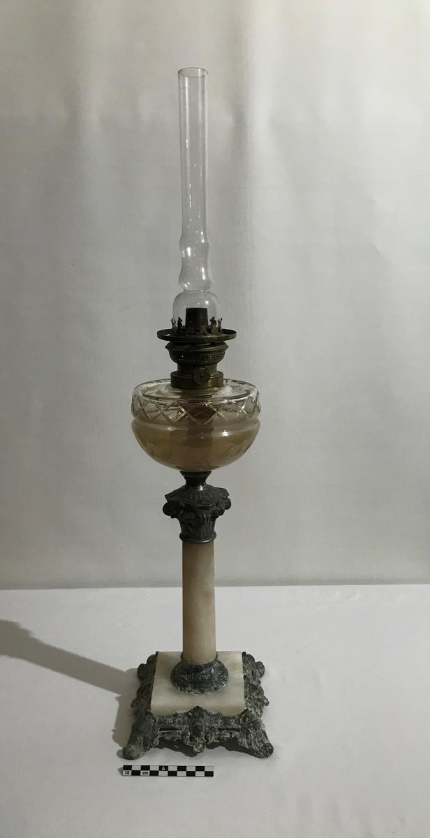 Høy oljelampe. Fint dekorert. Firkantet fot i marmor og messing. Kuppel og oljebeholder i dekorert glass.