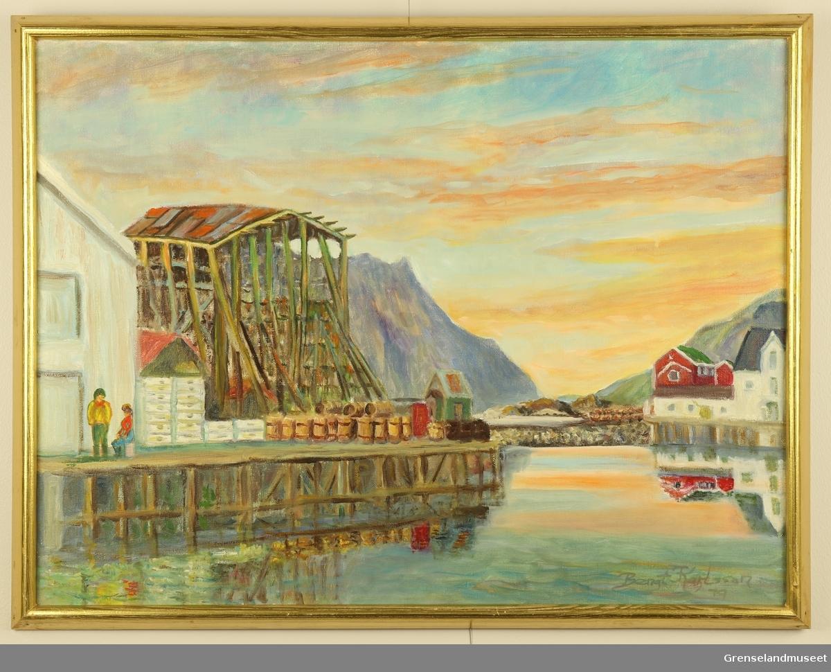 Kaianlegg, en mann står og en kvinne sitter på kaia. Tomme tønner og fiskekasser står foran en lagerbygning. Fjell i bakgrunnen.
