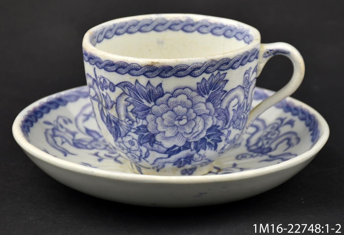 Kaffekopp med stora blommor i ljus lila, i botten av koppen IX (eller XI), i botten av fatet Lilas  (dekornamnet) inom blomkrans, inpressat Rörstrand. Ironstone.