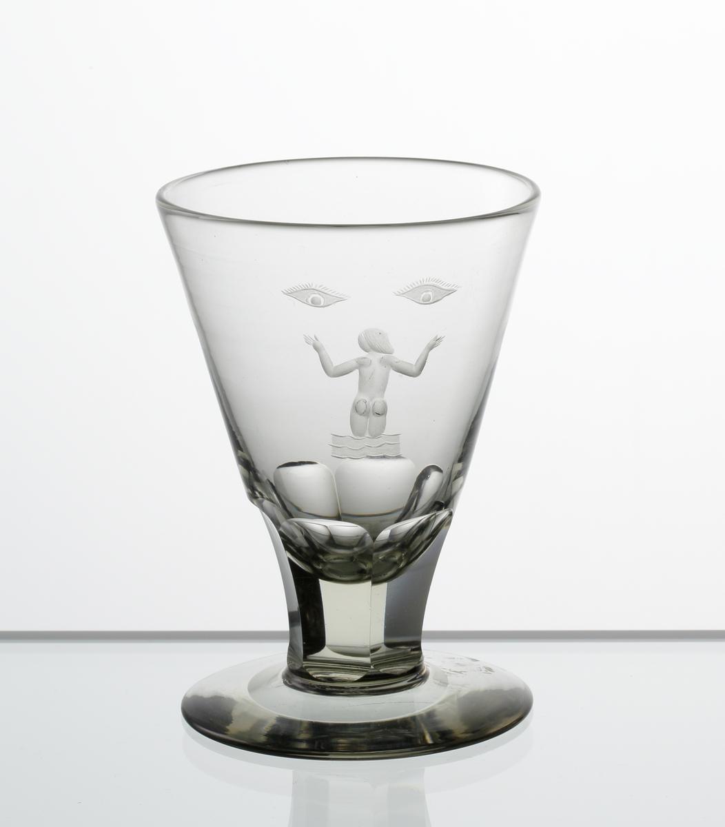 Design: Edward Hald. Brännvinsglas. Grågröntonad, konisk kupa med fasettslipat lågt ben på fot. Graverat motiv i form av badande kvinna och  ett ögonpar på kupan.