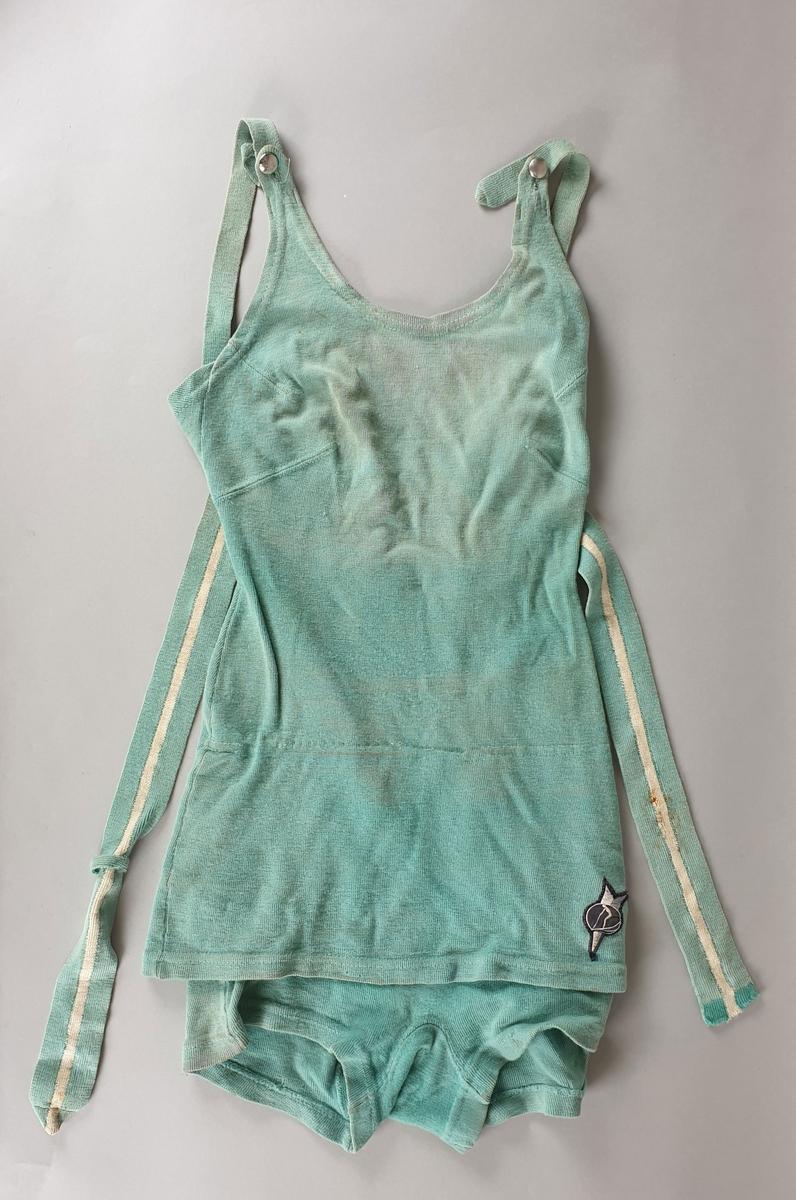 Grønn badedrakt for kvinne med skjørt. Skulderstropper med metallknapper, og belte. Merke på venstre hofte.