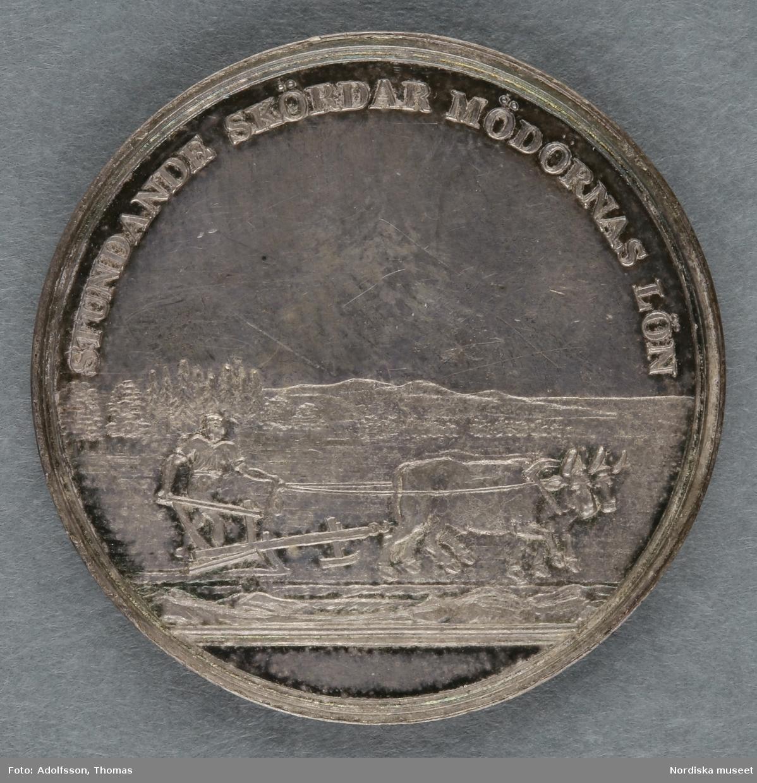 """Huvudliggare: """"Minnespenningar. 3 st. I silfver. Öfver Carl XIV Johan. a. Jfr. Hildebrand sid. 336, nr 29 b. Jfr. -""""- sid.337, nr 25 c. Jfr. -""""- sid 364, nr 77a""""  B: Minnespenning av silver, till minne av Carl XIV Johans kröning till kung Stockholms storkyrka den 11 maj 1818. På åtsidan kungens bröstbild och texten: """"CARL XIV JOHAN SV. OCH NORR: K: KRÖNT ÅR 1818"""". På frånsidan kungens valspråk: """"FOLKETS KÄRLEK MIN BELÖNING"""" inom en krans av hälften ek (symbolväxt för Norge) till hälften oliv (Sverige).  Denna penning kastades ut bland folket på stadens torg och öppna platser vid kröningen, enligt gammalt bruk. Carl XIV Johan var unionskung och kung över båda kungarikena Sverige och Norge. Se Hildebrand, del 2, nr.25. Jämför inv.nr. 29 574b, som är motsvarande minnespenning från Carl XIV Johans kröning i Trondheims domkyrka samma år. Maria Maxén/2005"""