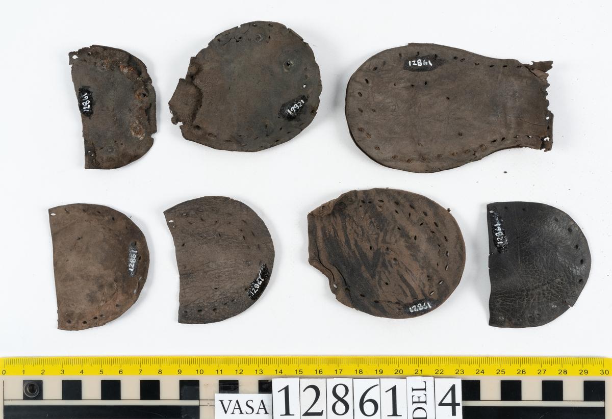 Två monterade stövlar samt delar och fragment från stövel. Eventuellt omfattar fyndnumret även delar och fragment från sko. Stövel till höger fot, fyndnummer 12861. Skaftet är skuret i ett stycke som har fästs samman med en söm på baksidan av stöveln. Skaftets övre del är något solfjädersformad, troligtvis för att det skall kunna vikas ned. Stövelskaftets övre del är något fragmentariskt. Ovanlädret är skuret i ett stycke. Skaftets insida har förstärkts med svart kartong av konserveringsenheten. Ovanlädret är monterat på svart kartong. Stövelbottnen består av spaltade sulor. På bottnens högra sida finns en laglapp med kvarsittande träpligg. På insidan av stöveln är hälen förstärkt med en bakkappa. Bottnen tycks inte vara komplett. Sulorna har fästs samman med tråd och lim av konserveringsenheten. Stövel till vänster fot, fyndnummer 12861:1. Skaftet är skuret i ett stycke som har fästs samman med en söm på baksidan av stöveln av konserveringsenheten. Skaftets övre del är något solfjädersformad, troligtvis för att det skall kunna vikas ned. Ovanlädret är skuret i ett stycke. Stöveln är något bättre bevarad än fyndnummer 12861. Stövelbottnen, fyndnummer 12861:2 ligger löst. Botten till vänster stövel, fyndnummer 12861:2. Stövelbottnen består av spaltade sulor samt en spaltad klacklapp. Sulorna är ritsade. Längs med ytterkanterna löper hål efter stygn och kvarsittande träpligg. På bottnens vänstra sida finns en laglapp med kvarsittande träpligg. Bottnen tycks inte vara komplett. Sulorna har fästs samman med tråd och lim av konserverinsenheten. Ett 130-tal delar och fragment från stövel, varav vissa delar möjligen härrör från skor. Bland delarna och fragmenten går bl a att urskilja sex stycken sulor, en del av en klack med kvarsittande träpligg, femton klacklappar, sju delar av inlägg, elva skurna läderremsor, nio träpligg samt en tråd eller ett snöre i form av tvinnad ull. Minst tre av sulorna härrör från höger stövelbotten. Troligtvis härrör de andra tre sulorna från v