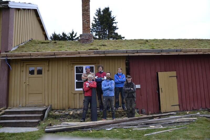 Bilde av arbeidsgjeng foran hus med torvtak (Foto/Photo)
