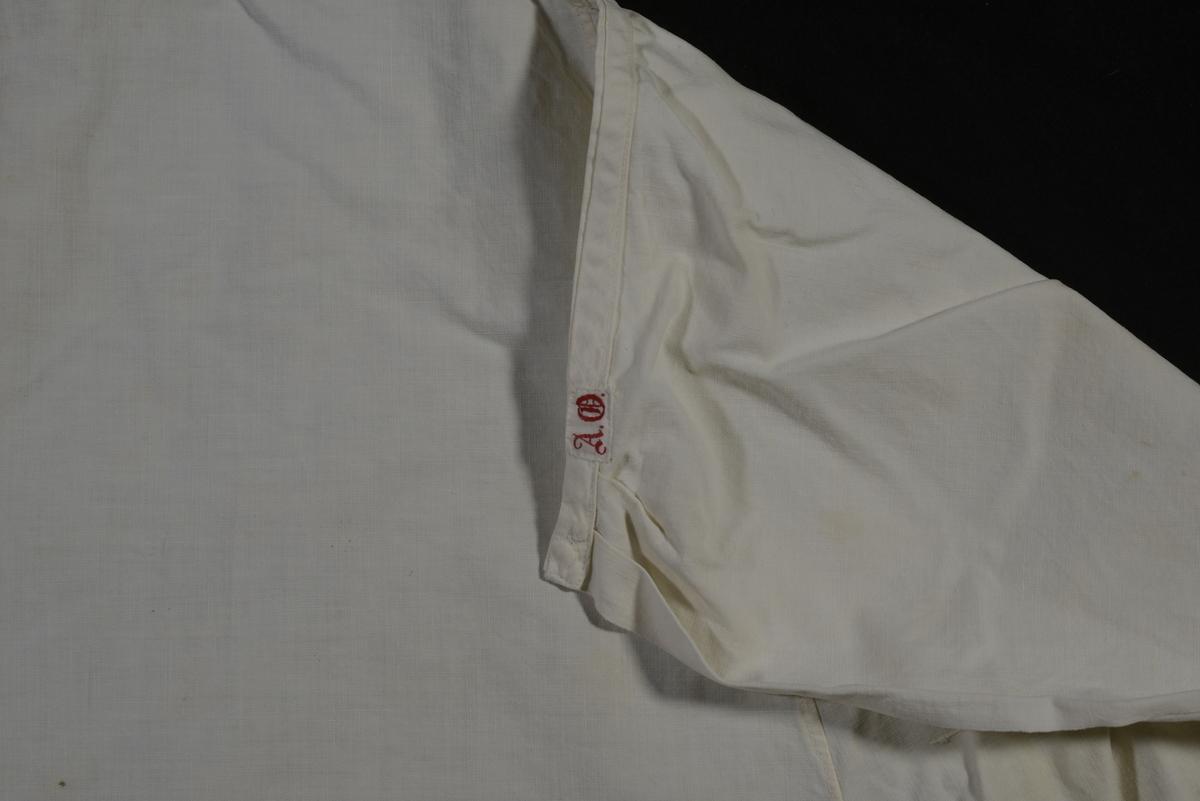 I vitt bomullstyg. Sytt med mittenplatta, infällda kilar och sidovåder. Bröstlapp med besparing runt halsen. Mått: Längd bak: 920 mm.