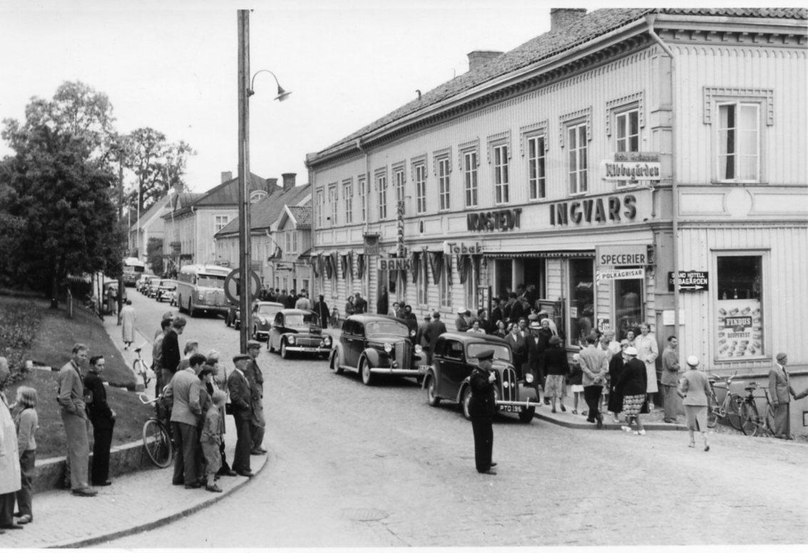 Tätt trafik rullar på Brahegatan norrut genom Gränna i samband med en solförmörkelse. En polis står i korsningen Ribbagårdsgränd och dirigerar trafiken. Mycket folk ute.