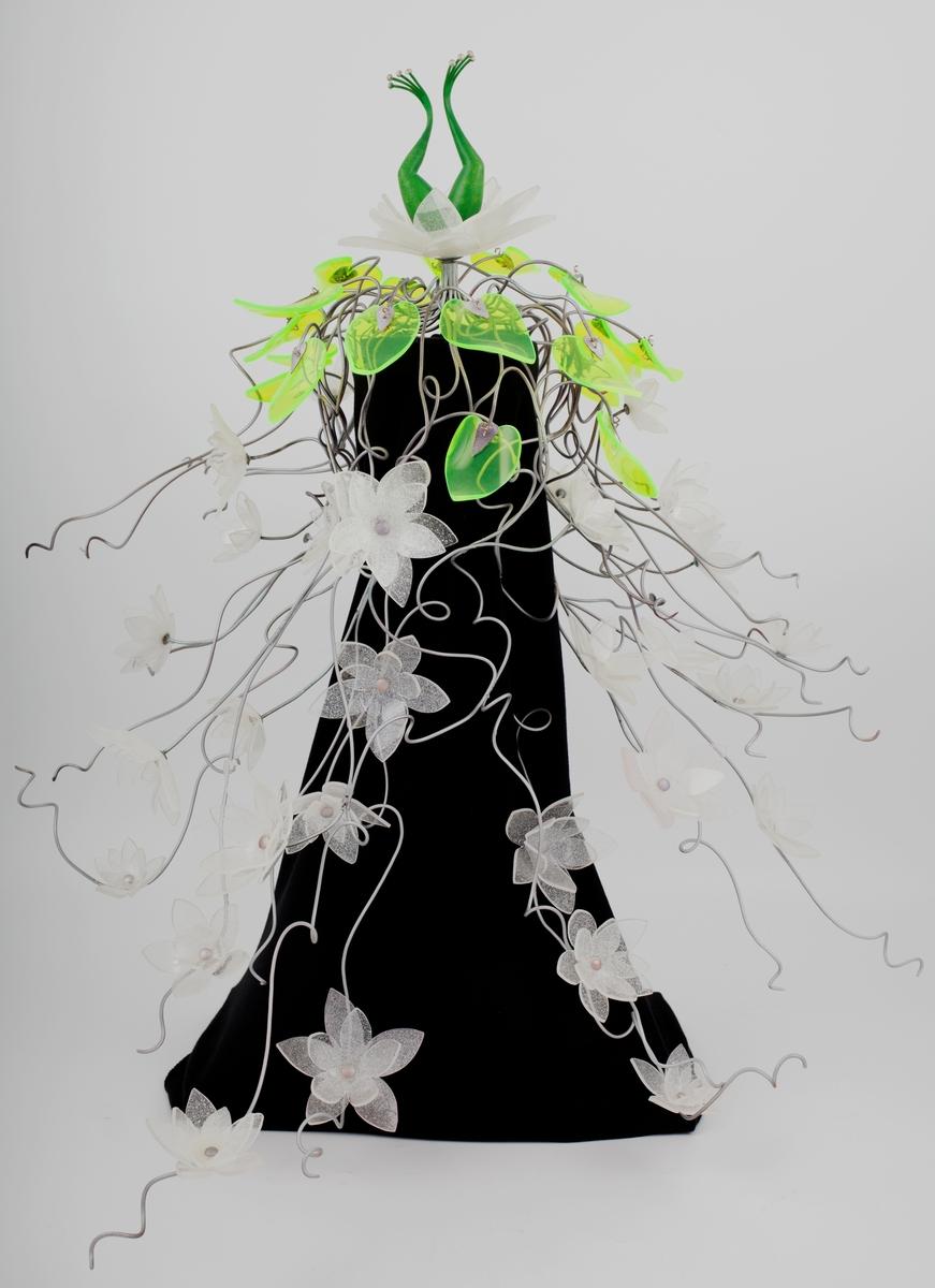 """Stort, eventyrinspirert hodesmykke med hvite vannliljeblomster og neongrønne blader i pleksiglass festet til tynne stenger av metall, som """"vokser"""" ut fra toppen av smykket og nedover på sidene i snirklete former og danner et slags slør. På toppen av smykket er det festet en stor hvit vannlilje der det stikker opp et par grønne froskeben."""