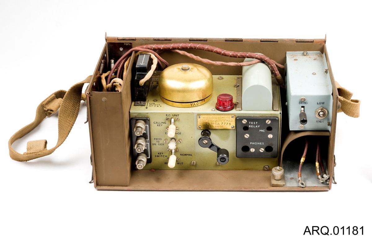 """Et apparat for telekommunikasjon mellom stasjoner av typen; Wireless Remote Control Units """"E"""" MK. II. Denne typen Kontroll-enhet er trådløs og bærbar. Den kan knyttes opp til ulike enheter trådløst, men for utvidede funksjoner må det kobles til noen andre apparater. Det mangler f.eks et oppkoblet rør til dette eksemplaret. Det kan man koble til denne enheten. På innsiden er det en utfyllende bruksanvisning til ulike typer oppkoblinger. Blikkboksen som holder telefonen er også utstyrt med en skulder-reim til å bære den. Blant bryterne ser man at man kan koble til telefonrør og mikrofon. På toppen er det montert en ringeklokke i messing. Navn og serienummer på enheten er festet med et gull-skilt ved bryter-panelet."""