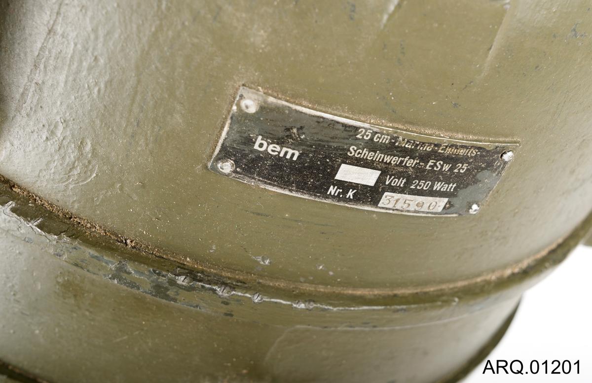 En lyskaster for å kommunisere med lyssignaler. Den har bærehondtaker 3 stk og et sikte på toppen. Lakkert olivengrønn og er skrudd fast til finerplater. Ledningen (strømkabelen) er kuttet av. Det står en rest av ledningen igjen.