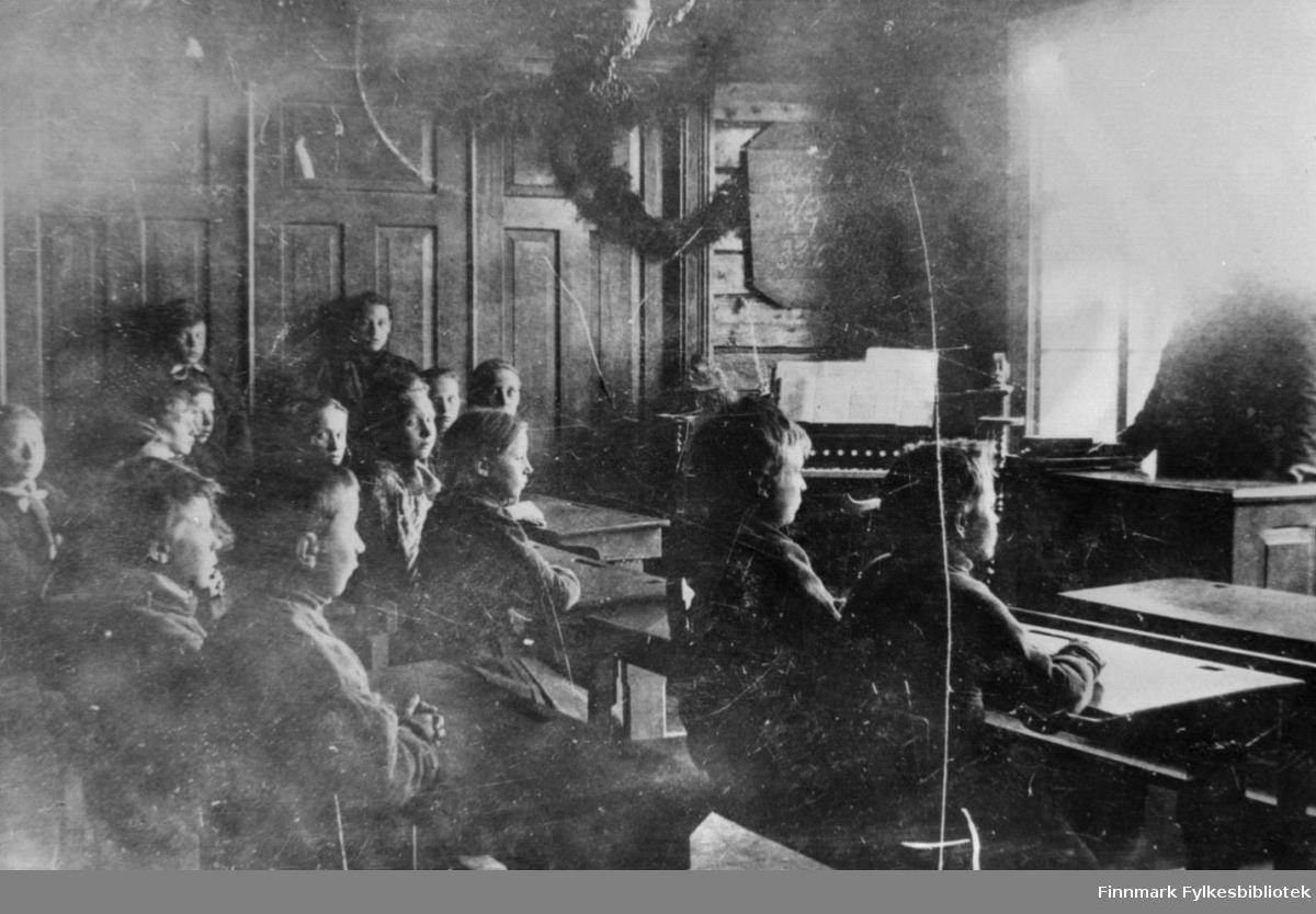 Bugøynes skole i Sør-Varanger. Interiør fra klasserom. Elever sitter ved siden skolepultene sine. Lærer er Richard Reinholdtsen.